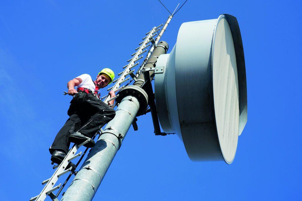 Mitarbeiter arbeitet an einer Richtfunk Antenne